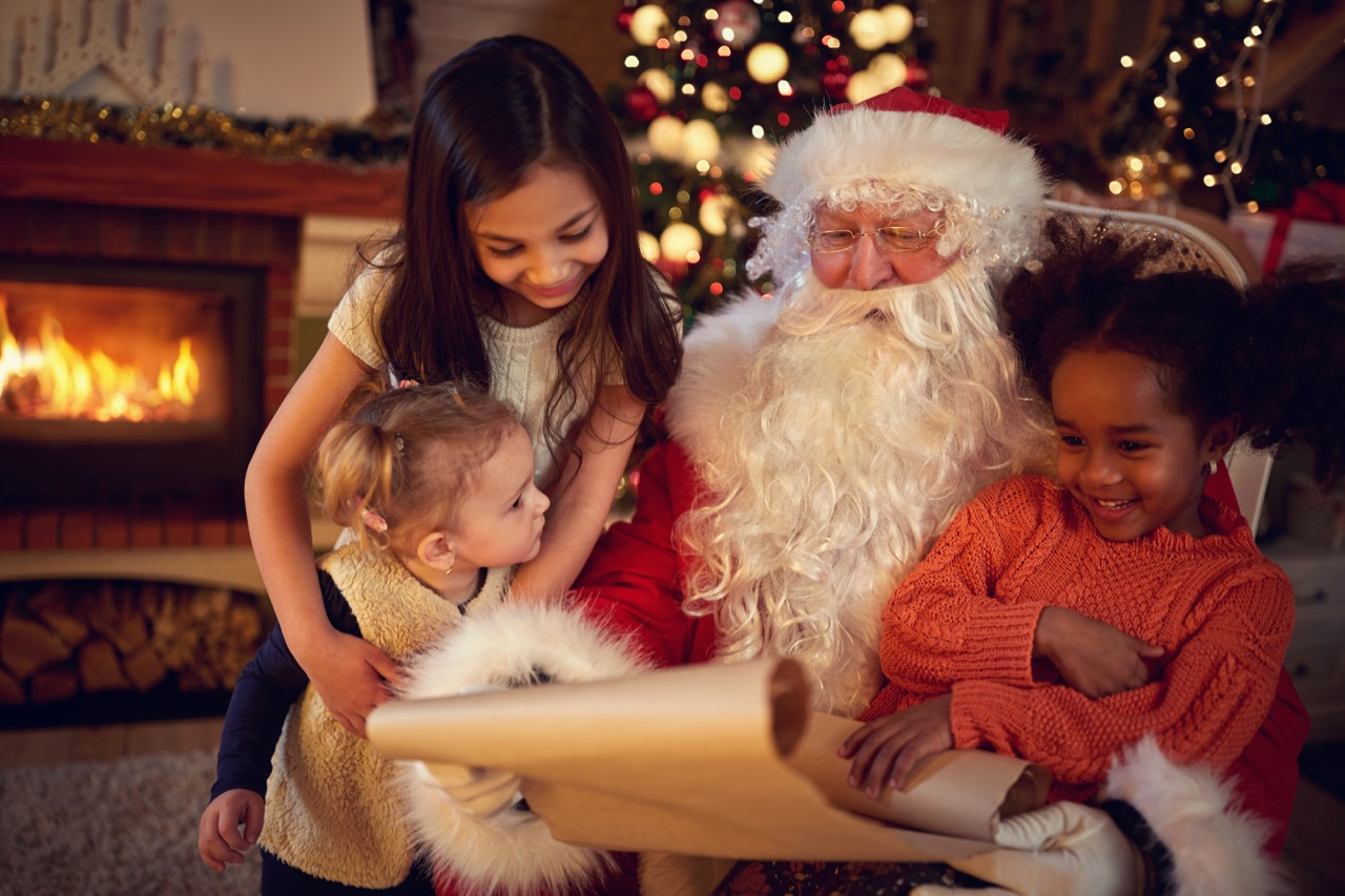 santa-claus-father-reading-wish-list-with-mixed-race-little-girls