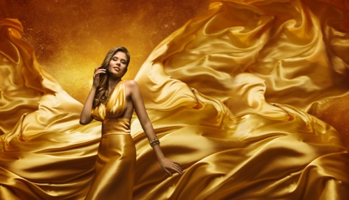 fashion-model-in-gold-dress--beauty-woman-posing-over-flying-waving-cloth--girl-with-yellow-dynamic-silk-fabric