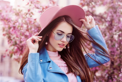 young-beautiful-fashionable-girl-wearing-stylish-blue-color-aviator-sunglasses--pink-suede-hat--earrings--biker-jacket.-model-posing-in-street-with-flowering-trees.-spring-fashion-concept