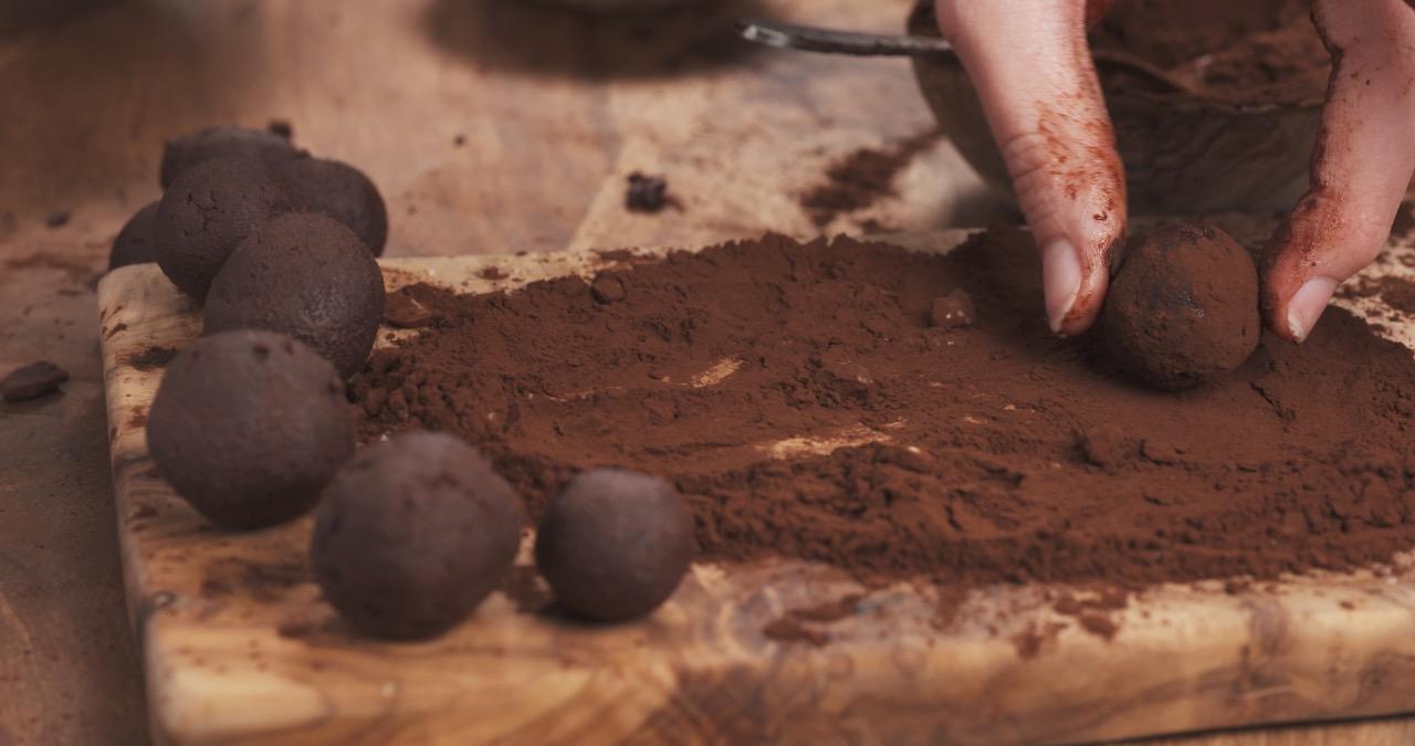female-hands-making-truffles-in-cocoa-powder-on-board
