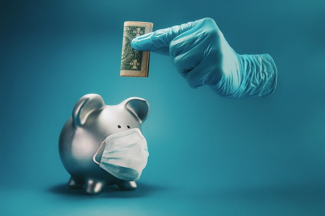 concept-of-saving-money-during-the-time-of-infectious-disease-pandemic.-a-hand-inside-protective--surgical-glove-holding-money-above-piggy-bank-with-face-mask