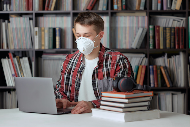 a-young-guy-in-a-surgical-mask-is-working-on-a-laptop-in-the-library-at-a-safe-distance-from-other-people