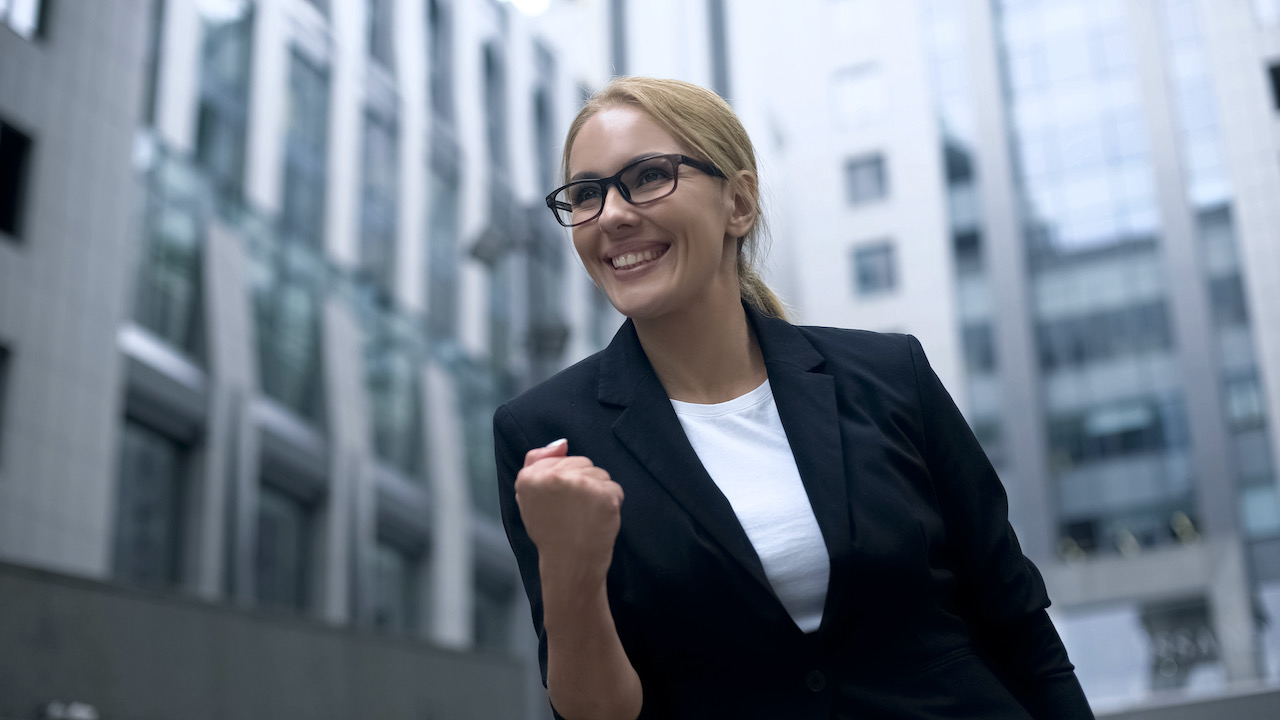 business-woman-showing-yes-gesture--rejoices-at-promotion-and-successful-career